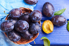 Fresh raw plums. Fresh juicy raw plums in a wicker basket at a blue wooden background. Top view. Concept photo. Universe in one plum Royalty Free Stock Image