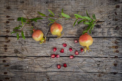 Fresh raw pomegranate. Cute small pomegranate on wooden background Royalty Free Stock Image