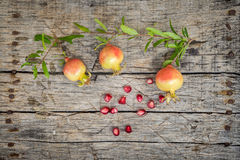 Fresh raw pomegranate. Cute small pomegranate on wooden background Stock Photo