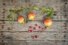 Fresh raw pomegranate. Cute small pomegranate on wooden background Royalty Free Stock Photography
