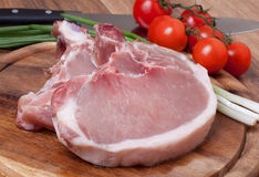 Fresh raw pork. Cutlet with tomatoes and onion Stock Photos