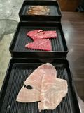 Fresh raw pork beef slice for grill serving on black tray which focus-on-foreground with blur background, Thin slices of pork beef. Freshness Japanese meat for Royalty Free Stock Photography