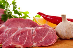 Fresh raw pork on board. With vegetables Royalty Free Stock Photo