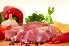 Fresh raw pork on board. With fresh vegetables, garlic, parslay, lemon and red chilli Royalty Free Stock Photography