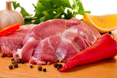 Fresh raw pork on board with fresh vegetables. Red chilli, lemon, garlic Royalty Free Stock Images