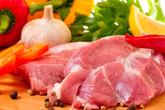 Fresh raw pork on board with fresh, vegetables. Fresh raw pork on board with fresh vegetables, garlic, red chilli, parslay, lemon, pepper Royalty Free Stock Image