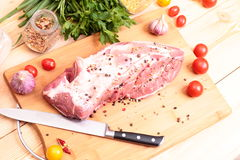 Fresh Raw Pork Chop. With tomatoes, greens, spices and garnet Stock Images