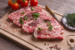 Fresh raw pork chop meat on cutting board Stock Image