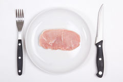 Fresh raw pork chop on a plate with fork and knife Stock Photos