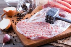 Fresh raw pork chops on chopping board. On wooden desk Royalty Free Stock Photography