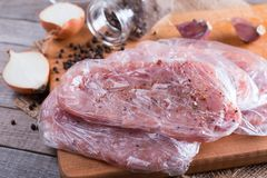 Fresh raw pork chops meat in a bag on chopping board on wooden desk. Fresh raw pork chops meat in a bag on chopping board on desk Stock Photo