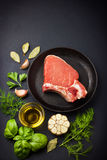 Fresh raw pork chops with spices and herbs. On black background, top view Stock Photography