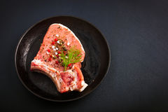 Fresh raw pork chops with spices and herbs. On black background, top view Royalty Free Stock Photos