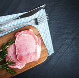 Fresh raw pork chops with spices and herbs. On a stone background Royalty Free Stock Photo