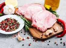 Fresh raw pork chops with spices and herbs. On a stone background Stock Photos