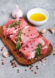 Fresh raw pork chops with spices and herbs. On a stone background Stock Photo