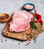 Fresh raw pork chops with spices and herbs. On a stone background Royalty Free Stock Photos