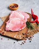 Fresh raw pork chops with spices and herbs. On a stone background Royalty Free Stock Images