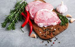 Fresh raw pork chops with spices and herbs. On a stone background Royalty Free Stock Photography