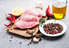 Fresh raw pork chops with spices and herbs. On a stone background Stock Image