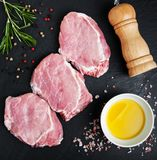 Fresh raw pork chops with spices and herbs. On a stone background Stock Photography