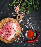 Fresh raw pork chops with spices and herbs. On a stone background Royalty Free Stock Image