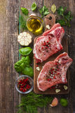 Fresh raw pork chops with spices and herbs. On wooden background, top view Stock Photography