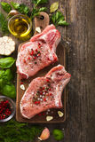 Fresh raw pork chops with spices and herbs. On wooden background, top view Royalty Free Stock Photography
