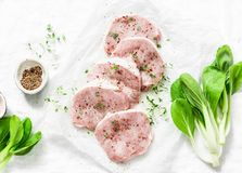 Fresh raw pork chops with spices and thyme and cabbage Bok Choi on light background, top view. Ingredients for cooking Stock Images