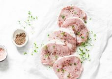 Fresh raw pork chops with spices and thyme on a light background. Top view Stock Image