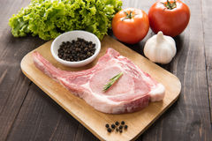 Fresh Raw Pork Chops and vegetable on wooden background. Royalty Free Stock Image