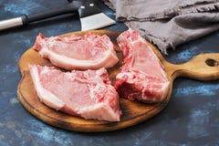 Fresh raw pork on a cutting board. Fresh raw pork on a cutting board, blue background Stock Photo