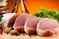 Fresh raw pork on cutting board. Fresh raw pork and vegetables on cutting board Stock Images