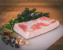 Fresh raw pork fat ready for gammoning on wooden cutting board, spices and herb Royalty Free Stock Images