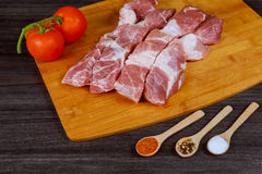 Fresh raw pork fat ready for gammoning on wooden cutting board, spices and herbs. Royalty Free Stock Image