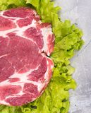 Fresh raw pork. On green lettuce leaves over table-top background Royalty Free Stock Images
