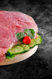Fresh raw pork ham meat decorated with vegetables on kitchen table plus clipping path Royalty Free Stock Images