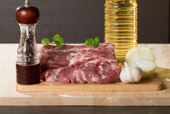 Fresh raw pork on light wooden cutting board. With onion, garlic, pepper and vegetable oil Stock Image