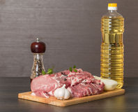 Fresh raw pork on light wooden cutting board. With onion, garlic, pepper and vegetable oil Royalty Free Stock Images