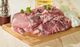 Fresh raw pork on light wooden cutting board. With onion, garlic, pepper and vegetable oil Stock Photo