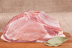 Fresh raw pork loin. With bay leaf on wooden board and on the background of sacking Royalty Free Stock Images
