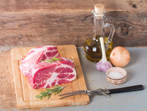 Fresh raw pork meat chops. On   cutting board on old wooden background Royalty Free Stock Image