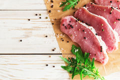 Fresh raw pork meat with salt, pepper and arugula. Stock Image