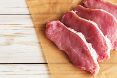 Fresh raw pork meat with salt, pepper and arugula. Royalty Free Stock Photography