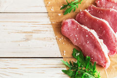 Fresh raw pork meat with salt, pepper and arugula. Stock Photo