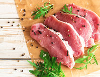 Fresh raw pork meat with salt, pepper and arugula. Stock Images