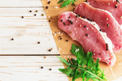 Fresh raw pork meat with salt, pepper and arugula. Stock Photos