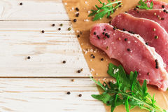 Fresh raw pork meat with salt, pepper and arugula. Royalty Free Stock Image
