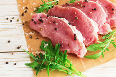 Fresh raw pork meat with salt, pepper and arugula. Ingredients for cooking. Food background with copy space Stock Photography