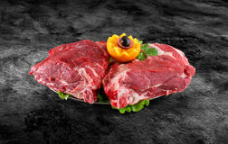 Fresh raw pork neck meat decorated with vegetables on kitchen table plus clipping path Stock Image